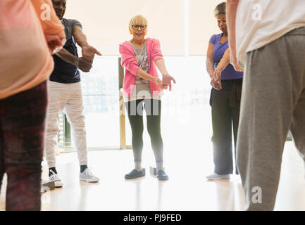 Active seniors stretching wrists in exercise class - Stock Image