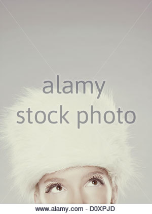 Young woman wearing fur hat and mascara, top section - Stock Image
