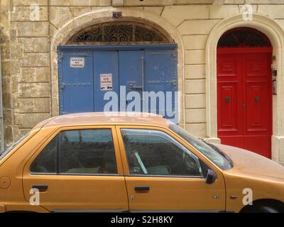 """""""What part of No Parking did you not understand?"""" One of many illegally parked cars in the old town of Valletta, Malta. - Stock Image"""