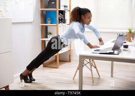 Side View Of A Happy Young Businesswoman Doing Push Up At Workplace - Stock Image