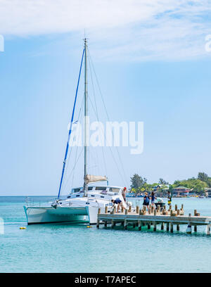 Catamaran takes on passengers and provisions at a dock in West Bay Roatan Honduras. - Stock Image