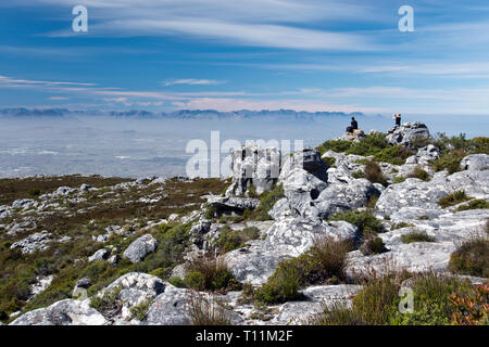 Hikers admire the view from the top of Table Mountain, the flat-topped mountain that overlooks Cape Town, South Africa. - Stock Image