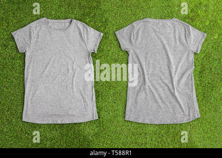 Front and back of grey melange empty T-shirt on grass background. Horizontal view. - Stock Image