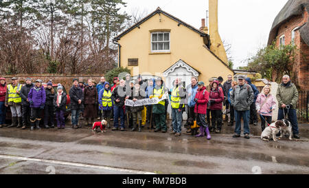 Walkers in outdoor clothing at the start of the Joseph Arch Centenary Walk outside his cottage in the village of Barford, with a banner. - Stock Image