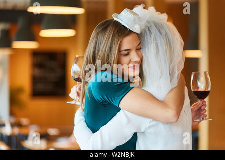 Bride and best friend happily hug each other at hen party - Stock Image