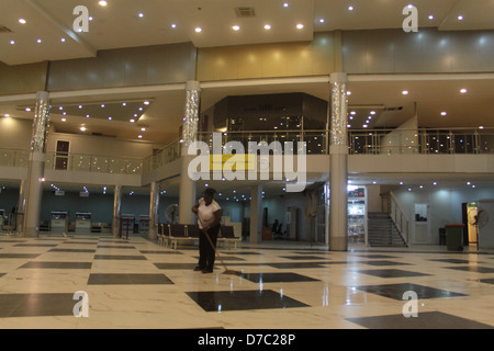 Cleaning of the departure lounge of Murtala Muhammed Airport, Ikeja, Lagos by a lady at night - Stock Image