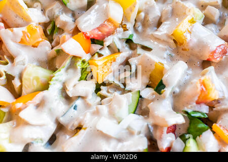 Closeup macro of fresh raw ceaser chopped vegetable salad with greens yellow bell peppers on romaine lettuce and white creamy dressing - Stock Image
