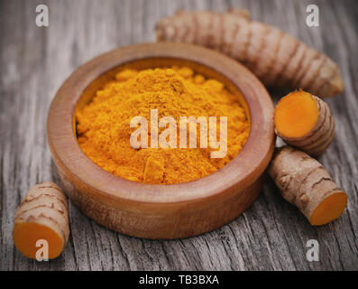 Raw turmeric with powder in a bowl on wooden surface - Stock Image