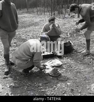 1960s, historical, scouts with leaders in the forest at an outdoor activity course perparing food for cooking, England, UK. - Stock Image