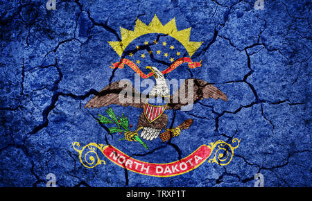 Flag of the state of North Dakota on dry earth ground texture background - Stock Image