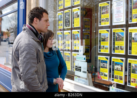 A young couple aspiring to buy their first home browse the listings in an estate agency window - Stock Image