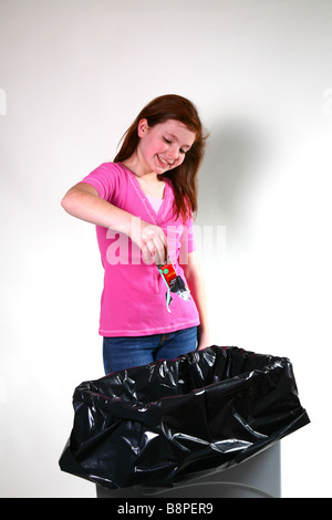 Girl throwing away a candy bar wrapper - Stock Image