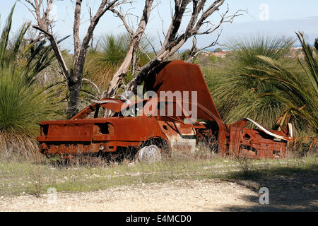 Stolen car, burnt out, rusted and abandoned or dumped in the Australian bush. - Stock Image