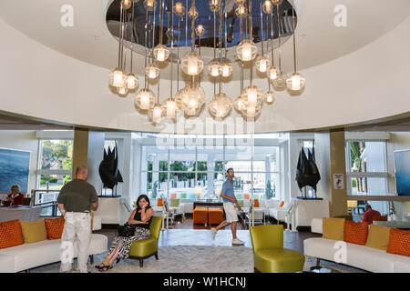 Fort Lauderdale Ft. Florida Hilton Fort Lauderdale Marina hotel lodging lobby guest man woman couple chandelier modern decor - Stock Image