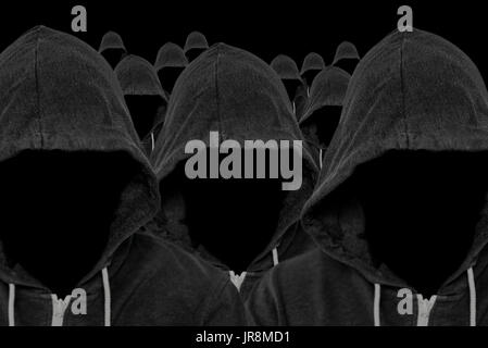 Mass of faceless mysterious and unknown hooded people with unseen faces and a black background - Stock Image