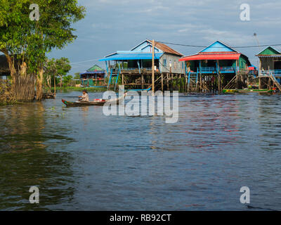 Villager paddling canoe from home in Kompong Phluk floating village a community of approximately 3000 mainly Khmer fishing inhabitants Siem Reap Cambo - Stock Image