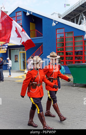 Vancouver, Canada.1st July, 2018. Two RCMP officers march in the annual Canada Day Parade on Granville Island, Vancouver, British Columbia. This year Canada Day celebrates the country's 151st birthday. Credit: John Mitchell/Alamy Live News - Stock Image