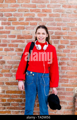 Young woman wearing red pullover, headphones in Verona - Stock Image