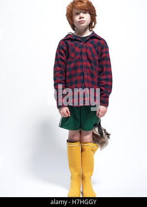 young boy with taxidermy raccoon head - Stock Image