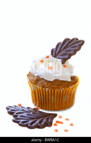 Pumpkin spice cupcake with vanilla frosting decorated with orange sprinkles and chocolate leaves for the Thanksgiving - Stock Image