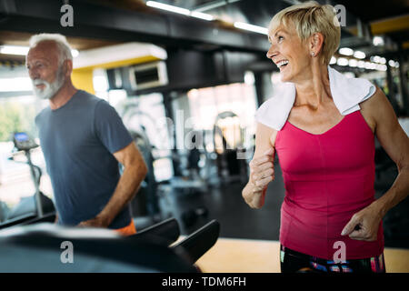 Fit senior sporty couple working out together at gym - Stock Image