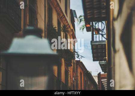 View of facades of residential houses on narrow street with sky behind with a lot of balconies, windows home plants, - Stock Image