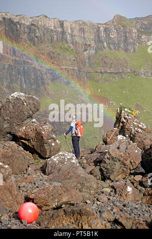 Mull, UK. 6th October 2018. Hill walker gazing at a rainbow on a beautiful autumnal day under the cliffs of Binnein Gorrie known locally as 'Gorrie's Leap' in a remote part of the Ross of Mull on the Hebridean island of Mull. Credit: PictureScotland/Alamy Live News - Stock Image