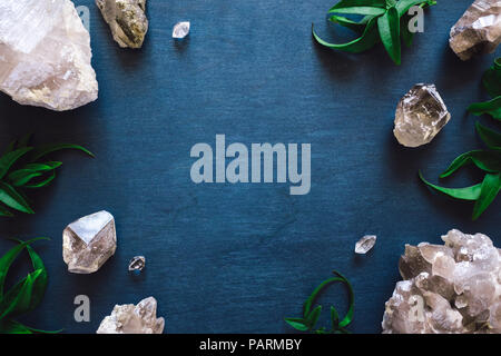 Frame with Clear and Smoky Quartz and Botanicals on Blue Table - Stock Image