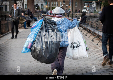 A middle aged Asian woman collecting deposit bottles in Greenwich Village, New York City. - Stock Image
