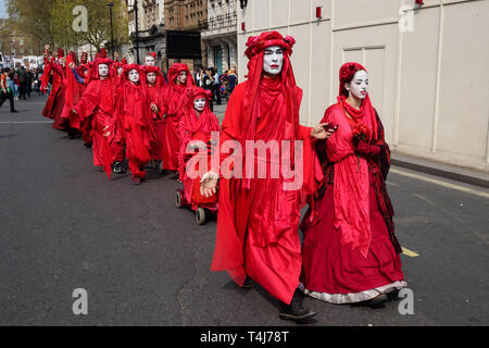 London, UK. 17th April 2019. A group dressed in red for the blood of the species which will become extinct processes down Parliament Street. Two days after Extinction Rebellion blocked the roads in Parliament Square it remains closed to traffic. Activities continue in and around the square with new protesters arriving. Credit: Peter Marshall/Alamy Live News - Stock Image