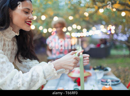 Woman lighting candles for dinner garden party - Stock Image
