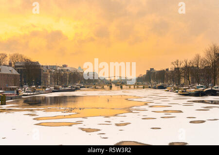 Winter in Amsterdam with frozen canal, snow and holes in ice because of cold wind. - Stock Image