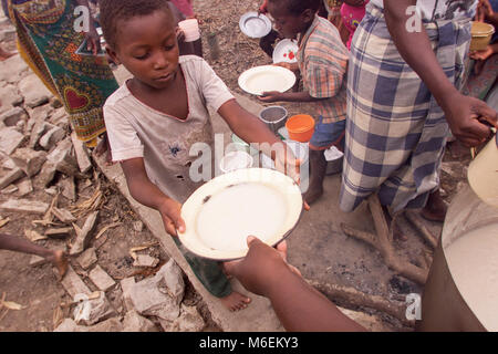 Floods in Mozambique  March 2000; A young boy takes a bowl maize porridge made with relief supplies at Pande camp - Stock Image
