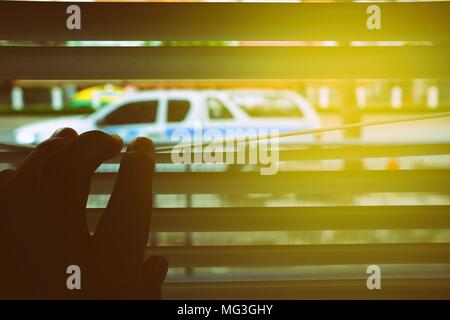 Hand Opening Window Blind with Sunlight Beam to See Car outside House. - Stock Image