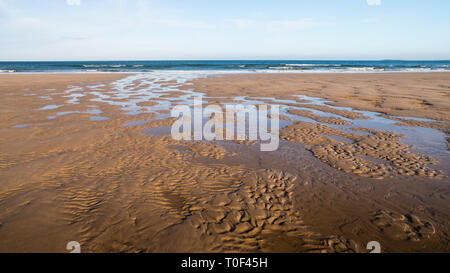 A bright sunny day on the beach with a stream crossing the sand towards the sea. - Stock Image