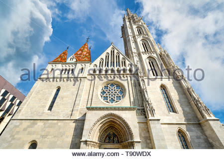 The front facade and rose window of Matthias Church at Buda's Castle Complex in Budapest Hungary on a sunny day - Stock Image