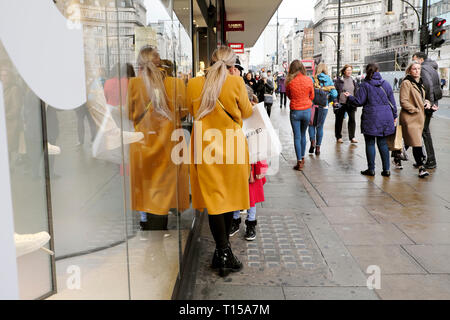 Rear back view of woman in fashionable yellow gold wool coat reflection in a shop window & shoppers on Oxford Street in Central London UK KATHY DEWITT - Stock Image