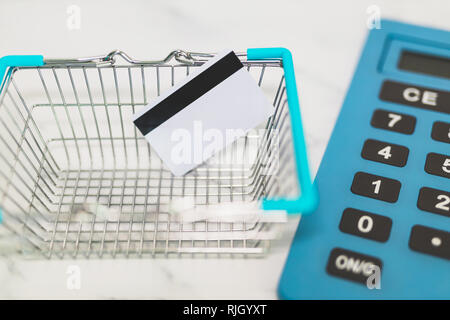 payment card into shopping basket and huge calculator in the background, concept of shopping budget - Stock Image