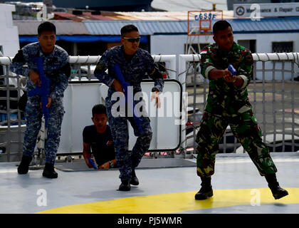 180829-N-QV906-0275 MANILA, Philippines (August 29, 2018) An Indonesia Navy Sailor and Philippine Coast Guardsmen practice tactical procedures during a Visit, Board, Search, and Seizure seminar as part of  Southeast Asia Cooperation and Training (SEACAT) 2018 aboard Philippine Coast Guard Headquarters in Manila, Philippines. This is the 17th annual SEACAT exercise and includes participants from the U.S., Brunei, Bangladesh, Thailand, Philippines, Singapore, Vietnam, Malaysia and Indonesia. (U.S. photo by Mass Communication Specialist 1st Class Micah Blechner/RELEASED) - Stock Image