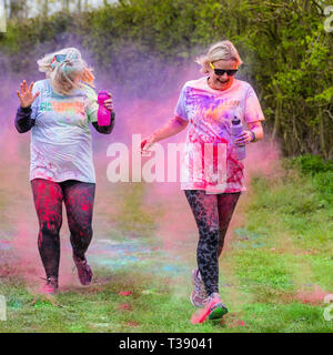 Two women runners being covered in paint on Macmillan cancer charity 5K color fun run. - Stock Image