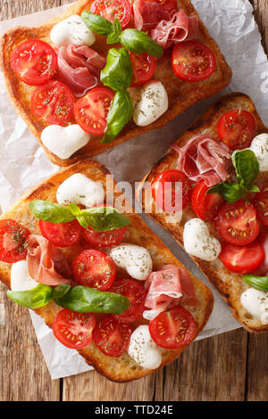 Ciabatta sandwiches with mozzarella, tomatoes, ham and basil close-up on the table. Vertical top view from above - Stock Image