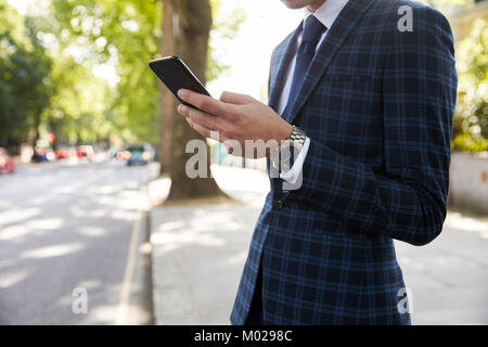 Businessman standing in street using smartphone, mid section - Stock Image