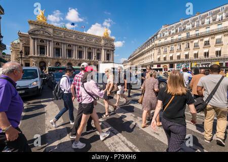 Paris, France - 25 June 2018: A crowd of people crossing Rue de la Paix near Paris Opera Garnier. - Stock Image