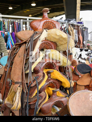 Stack of hand made western leather horse saddles ready for sale at a rodeo in Montgomery Alabama, USA. - Stock Image