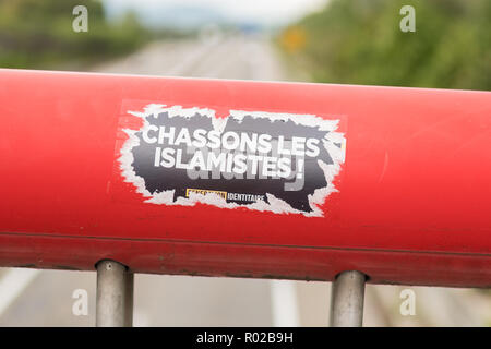 Generation Identitaire sticker Chassons Les Islamists on bridge in Colmar, France, Europe - Stock Image