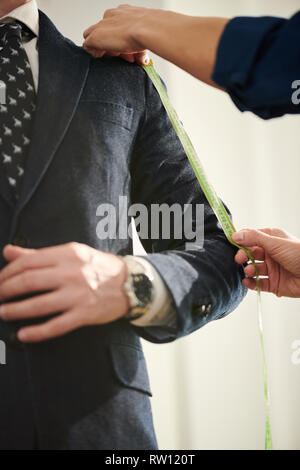 Taking measures of sleeve - Stock Image