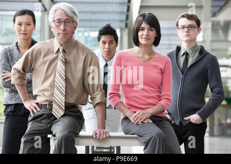 A team portrait of a mixed race group of business people with an Asian businessman in the lead. - Stock Image