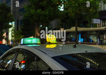 A light on the roof of a taxi cab lit to show it's available to hire at a cab rank in a Japanese city - Stock Image
