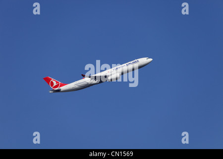 Turkish Airlines Airbus A330-343X TC-JNO climbing away from Heathrow airport - Stock Image