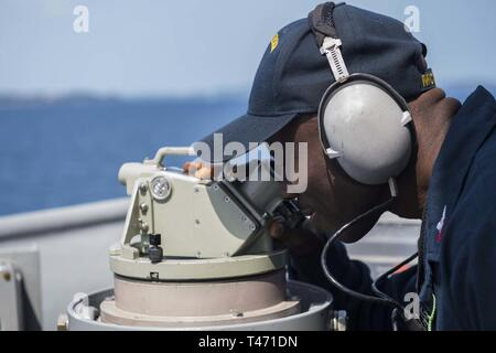 PHILIPPINE SEA (March 14, 2019) Personnel Specialist 1st Class Clement Aribisala tracks the ships bearing using a telescopic alidade as the Avenger-class mine countermeasures ship USS Pioneer (MCM 9) conducts a mine hunting training exercise. Pioneer, part of Mine Countermeasure Squadron 7, is operating in the U.S. 7th Fleet area of operations to enhance interoperability with partners and serve as a ready-response platform for contingency operations. - Stock Image